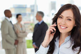 Young smiling businesswoman on the phone and tilting her head to — Stock Photo