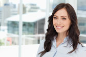 Young smiling executive woman standing upright in front of the w — Stock Photo
