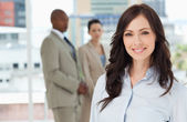 Young smiling businesswoman standing in front of her colleagues — Stock Photo