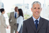 Mature smiling manager standing in front of his business team — Stock Photo