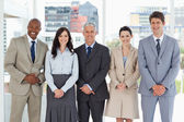 Smiling business team standing upright side by side with their h — Stock Photo