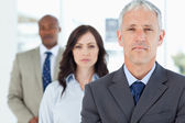 Mature and serious manager standing upright and followed by two — Stock Photo