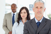 Young businesswoman standing upright between a colleague and her — Stock Photo