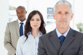 Young and serious businessman following two members of his team — Stock Photo