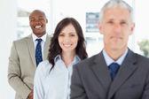 Mladý usmívající se zaměstnanec stojí vzpřímeně a po jeho tým — Stock fotografie