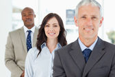 Three smiling business standing upright and looking ahead — Stock Photo