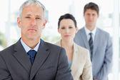 Ernsthafte und ausgereifte manager stehen aufrecht vor seinem team — Stockfoto