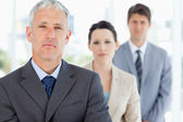 Serious and mature manager standing upright in front of his team — Stock Photo