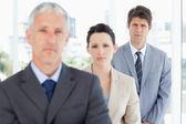 Joven ejecutivo serio tras su equipo de negocios — Foto de Stock