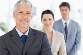 Mature manager followed by two young business — Stock Photo
