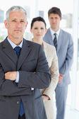 Serio gestione attraversando le braccia davanti al suo team di business — Foto Stock