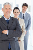 Smiling mature businessman standing upright in front of his youn — Stock Photo
