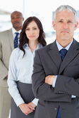 Mature manager crossing his arms seriously in front of two membe — Stock Photo