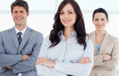 Young smiling executive woman crossing her arms in front of two — Stock Photo