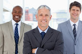 Mature director standing upright in front of his two smiling exe — Stock Photo