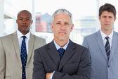 Ernstige volwassen manager staande voor zijn twee kaderleden — Stockfoto
