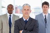 Serious mature manager standing in front of his two executives — Stock Photo