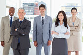 Smiling executive standing in the middle of the bright room amon — Stock Photo