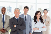 Five business crossing their arms in front of a bright wi — Stock Photo