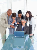 Four young executives attentively looking at the laptop screen — Stock Photo