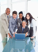 Four business standing behind their manager proudly showi — Stock Photo