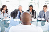 Four business sitting at the desk while attentively liste — Stock Photo