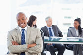 Young manager laughing while sitting in front of his team and cr — Stock Photo