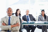 Young businessman crossing his arms with his team in the backgro — Stock Photo