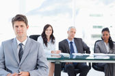 Earnest executive sitting in front of his team in a bright room — Stock Photo