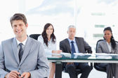Smiling young businessman sitting in front of his team and looki — Stock Photo