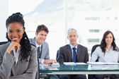 Confident executive sitting in a meeting room while her team is — Stock Photo