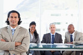 Stern businessman crossing his arms while his team in the back i — Stock Photo