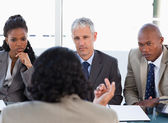 Three business attentively listening to a speaker in a me — Stock Photo