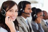Sorridente funcionário trabalhando com um fone de ouvido enquanto olha para a cam — Foto Stock