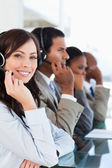 Smiling call centre agent looking at the camera while working ha — Stock Photo