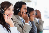 Smiling call centre employee working while accompanied by her te — Stock Photo