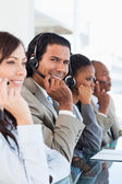 Young smiling call centre worker working among his business team — Stock Photo