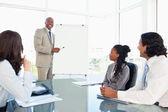 Smiling young executive giving a presentation — Stock Photo