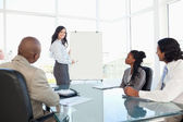 Businesswoman giving a presentation while her co-workers are lis — Stock Photo