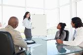 Empresaria dando una presentación mientras que sus compañeros de trabajo son lis — Foto de Stock