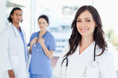 Młoda pielęgniarka stoi przed dwoma kolegami — Zdjęcie stockowe
