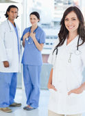 Smiling female doctor standing upright with her hands in her poc — Stock Photo
