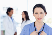 Serious medical intern looking at the camera while her team is b — Stock Photo