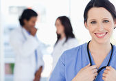 Confident nurse standing upright accompanied by her team in the — Foto Stock