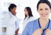 Pewność pielęgniarka stojącą towarzyszy jej zespół w — Zdjęcie stockowe