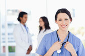 Smiling medical intern with her hair tied back standing in front — Stock Photo