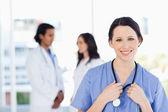 Souriant stagiaire médicale avec ses cheveux attachés dos debout devant — Photo