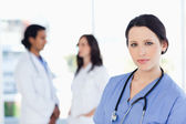 Calm nurse standing upright with her stethoscope around her neck — Stock Photo