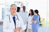 Volwassen arts wijzend op iets op zijn klembord — Stockfoto