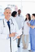 Lachende arts wijzen op een woord op zijn klembord — Stockfoto
